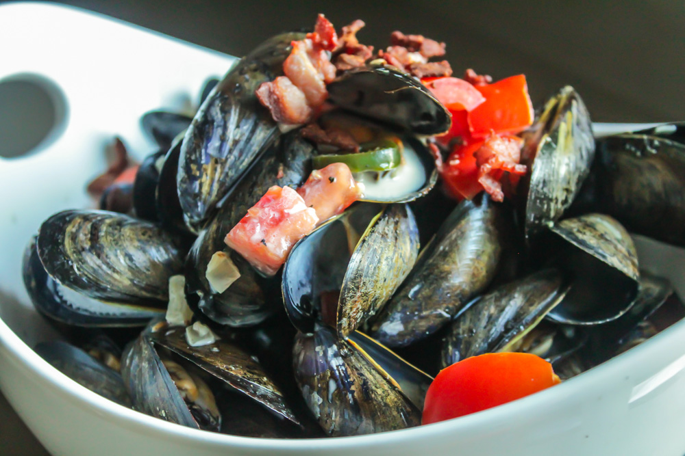 ... / Spicy Mussels in a White Wine Cream Sauce with Bacon and Tomatoes